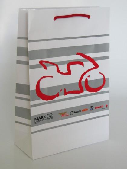 Papiertragetaschen mit eingeknoteten Baumwollkordeln in rot und Glanzplastifizierung