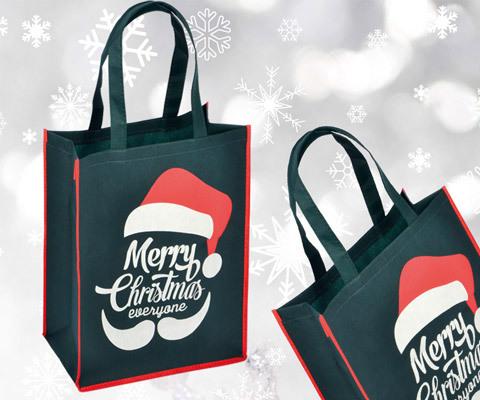 Weihnachtstaschen aus PP Woven die Taschen wurden grün eingefärbt mit roten ränder abgestppt mit Weihnachtsmotiv Merry Christmas in weiß mit roter nikolaus Mütze