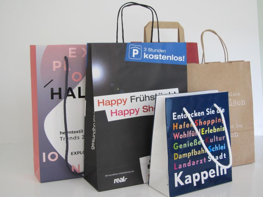 Tragetaschen aus Papier in verschiedenen Grössen und unterschiedlichen Griff variationen bedruck mit Firmen Logo